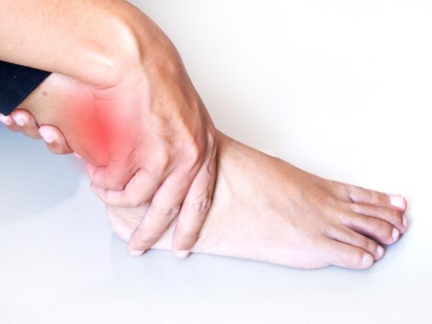 Jovem mulher asiática com dor no tornozelo e lesão na perna aguda. conceito de cuidados de saúde médico.