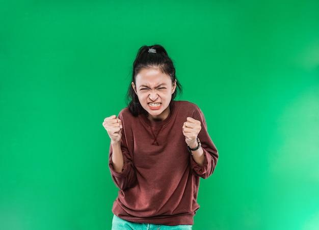 Jovem mulher asiática com expressão de raiva no rosto enquanto cerrou os punhos e ergueu as duas mãos isoladas sobre um fundo verde