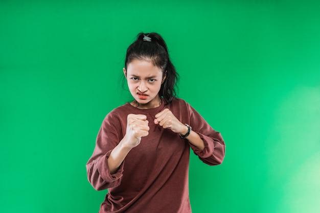 Jovem mulher asiática com expressão de raiva no rosto enquanto cerrou os punhos e ergueu as duas mãos sobre um fundo verde