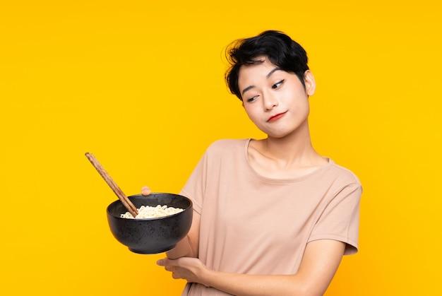 Jovem mulher asiática com expressão triste, segurando uma tigela de macarrão com pauzinhos
