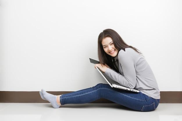 Jovem mulher asiática com laptop sentado na sala de estar. carinha feliz.
