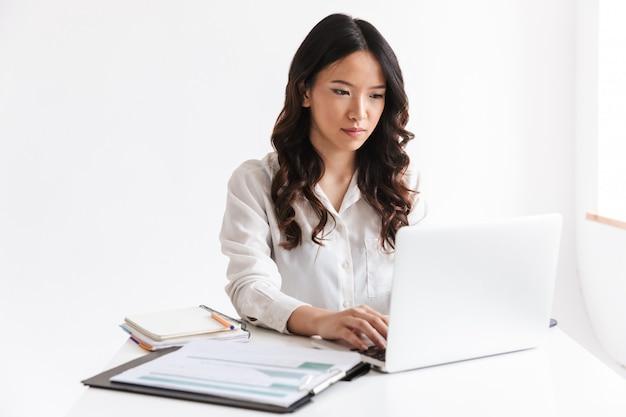 Jovem mulher asiática com longos cabelos escuros sentado à mesa e trabalhando com documentos e laptop