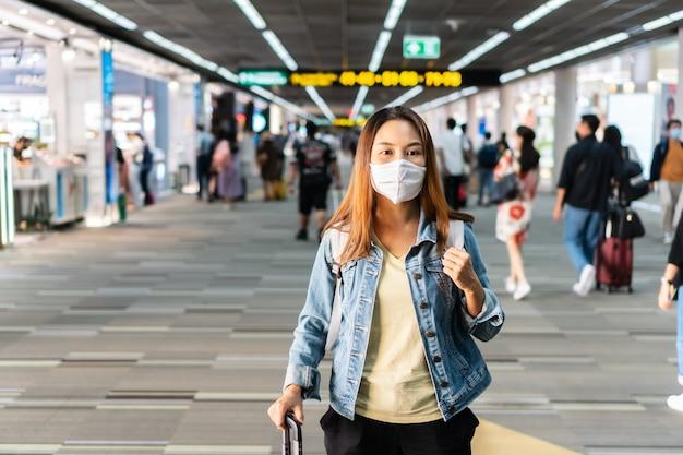 Jovem mulher asiática com máscara facial, caminhando no terminal do aeroporto. conceito de cuidados de saúde e proteção.