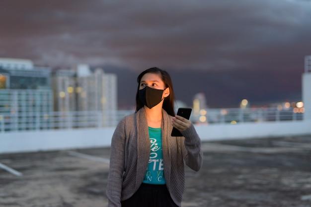 Jovem mulher asiática com máscara pensando enquanto estiver usando o telefone durante tempestades ao ar livre