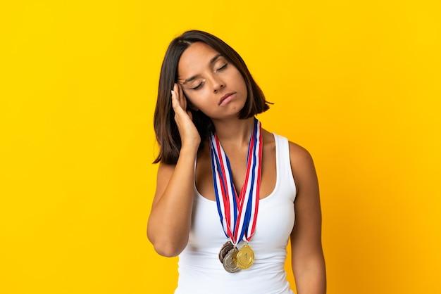 Jovem mulher asiática com medalhas isoladas em branco com dor de cabeça