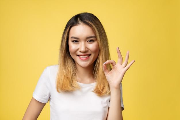 Jovem mulher asiática com o isolado aprovado do gesto do sinal sobre o fundo amarelo.