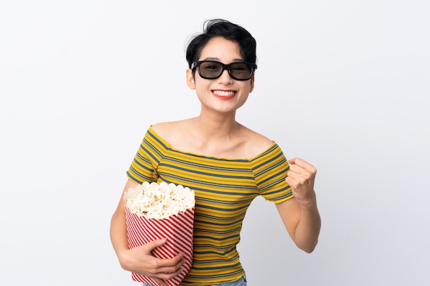 Jovem mulher asiática com óculos 3d e segurando um grande balde de pipocas