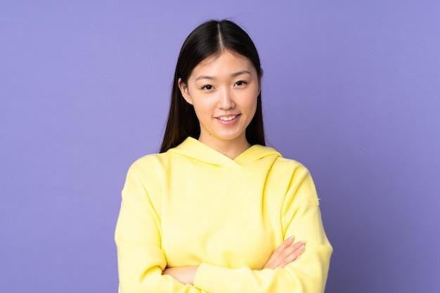 Jovem mulher asiática com os braços cruzados na posição frontal