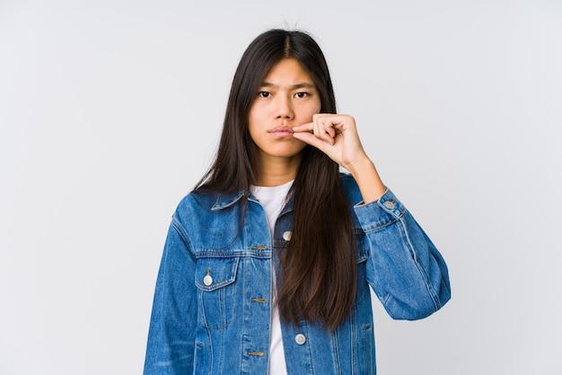 Jovem mulher asiática com os dedos nos lábios, mantendo um segredo.
