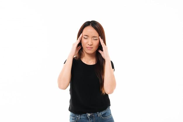 Jovem mulher asiática com os olhos fechados, tocando a cabeça