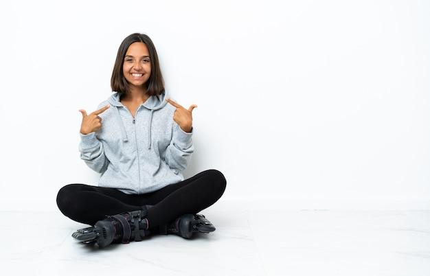 Jovem mulher asiática com patins no chão fazendo um gesto de polegar para cima
