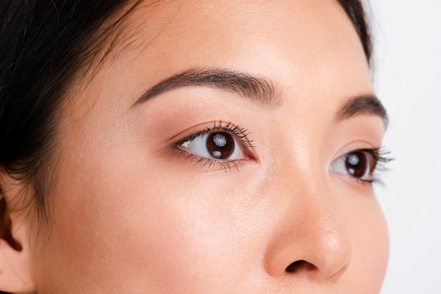 Jovem mulher asiática com pele clara, olhando para longe