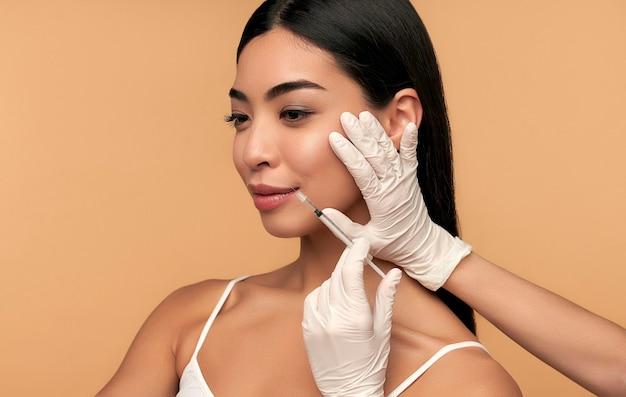Jovem mulher asiática com pele limpa e radiante recebe injeções de botox para endurecimento do contorno, aumento dos lábios em bege