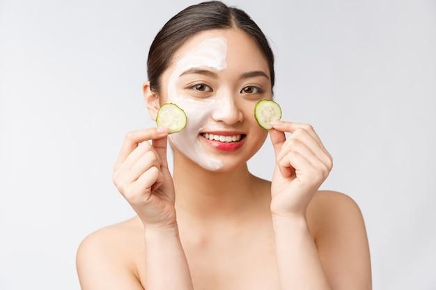 Jovem mulher asiática com pepino nos olhos