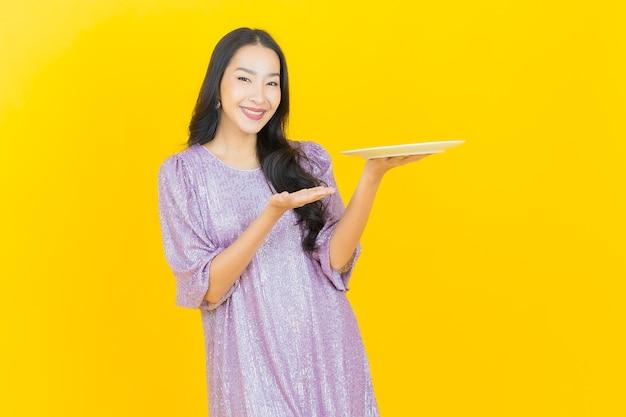 Jovem mulher asiática com prato vazio