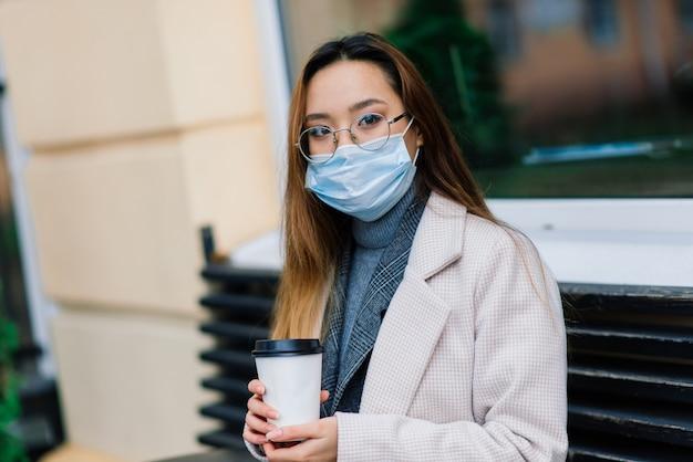 Jovem mulher asiática com proteção facial de máscara cirúrgica. ela se desloca entre a casa e o trabalho na cidade