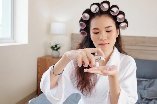 Jovem mulher asiática com rolos de cabelo na cabeça aplicando soro hidratante