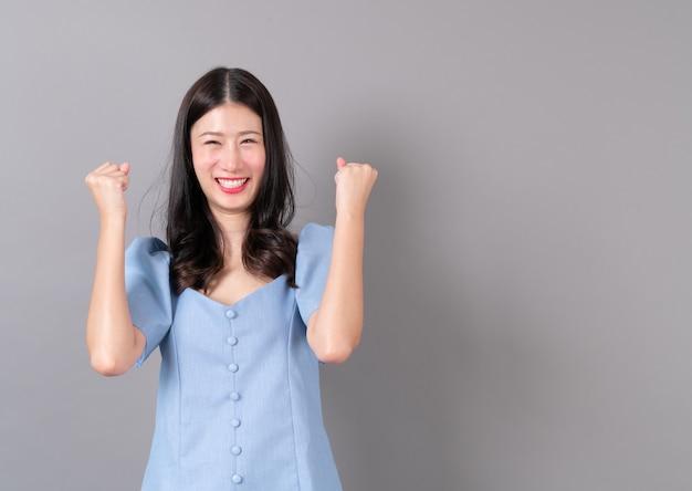 Jovem mulher asiática com rosto feliz e animado em cinza
