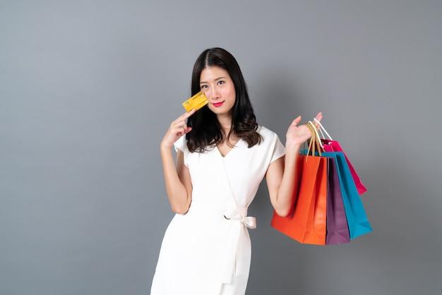 Jovem mulher asiática com rosto feliz e mão segurando sacolas de compras e cartão de crédito na cinza