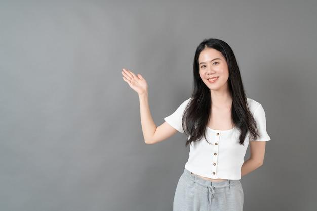 Jovem mulher asiática com rosto sorridente e mão se apresentando ao lado com fundo cinza