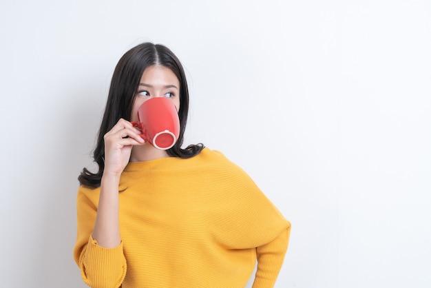 Jovem mulher asiática com suéter amarelo segurando uma xícara de café vermelha, cheira bem e aproveita o café com parede branca
