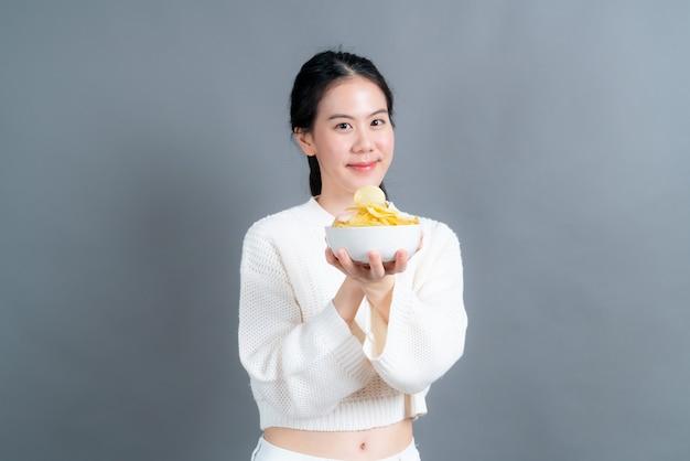 Jovem mulher asiática com suéter branco comendo batatas fritas