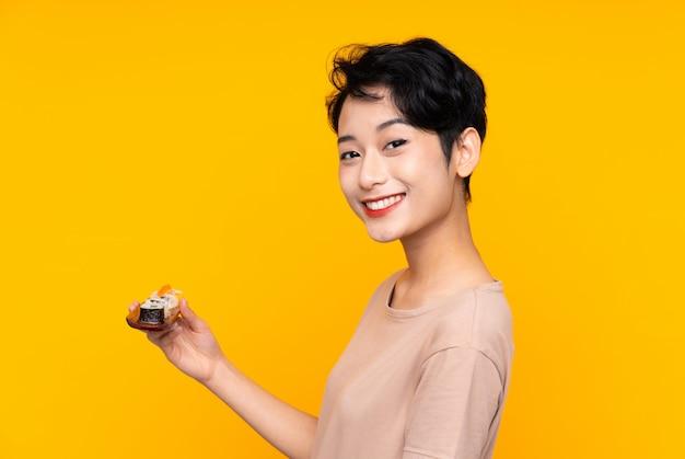 Jovem mulher asiática com sushi sorrindo muito
