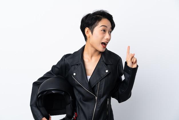 Jovem mulher asiática com um capacete de moto sobre parede branca isolada, com a intenção de realizar a solução enquanto levanta um dedo