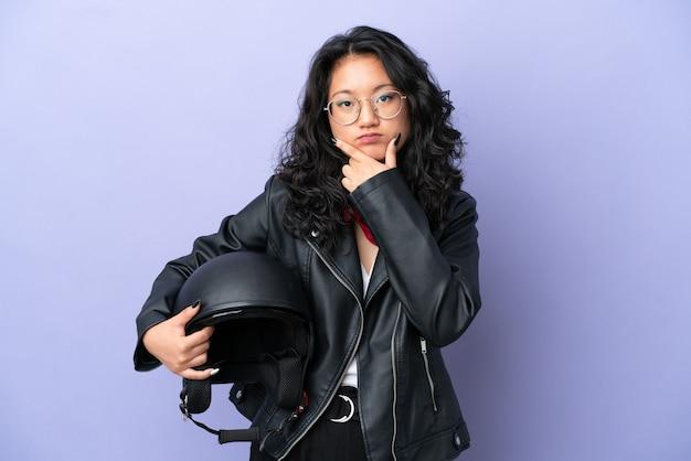 Jovem mulher asiática com um capacete de motocicleta isolada em um fundo roxo pensando