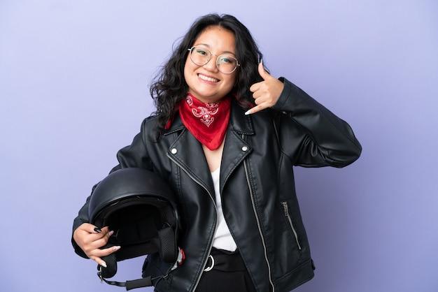 Jovem mulher asiática com um capacete de motocicleta isolado no fundo roxo, fazendo gesto de telefone. ligue-me de volta sinal