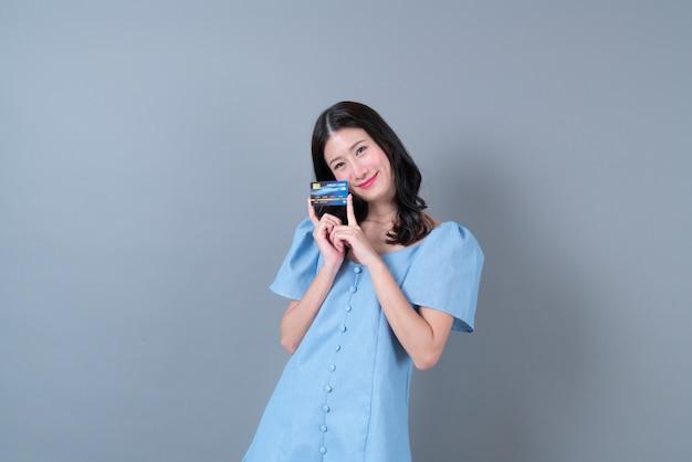 Jovem mulher asiática com um rosto feliz e uma mão segurando um cartão de crédito em um vestido azul na parede cinza