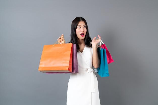 Jovem mulher asiática com uma cara feliz e uma mão segurando sacolas de compras