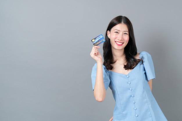 Jovem mulher asiática com uma cara feliz e uma mão segurando um cartão de crédito em um vestido azul cinza