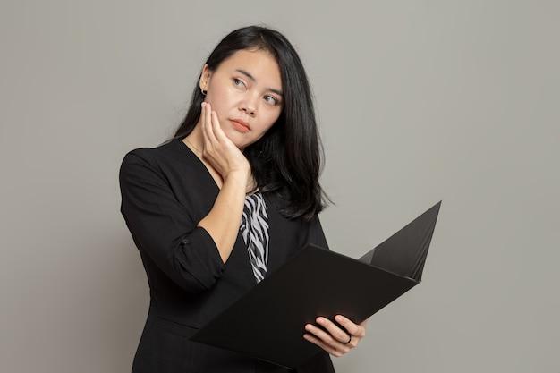Jovem mulher asiática com uma expressão facial ansiosa enquanto segura uma pasta