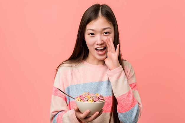 Jovem mulher asiática com uma tigela de cereal gritando animado para a frente.