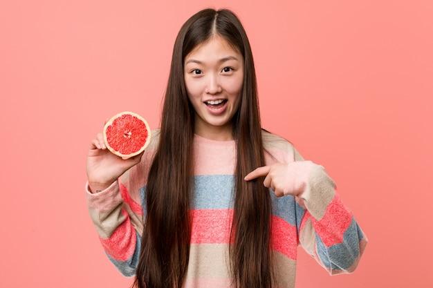 Jovem mulher asiática com uma toranja surpreendeu apontando para si mesmo, sorrindo amplamente.
