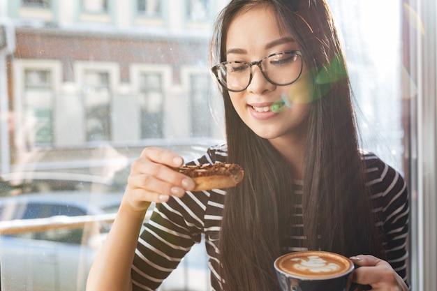 Jovem mulher asiática comendo bolo no peitoril da janela