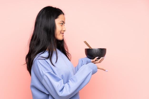 Jovem mulher asiática comendo macarrão sobre fundo isolado