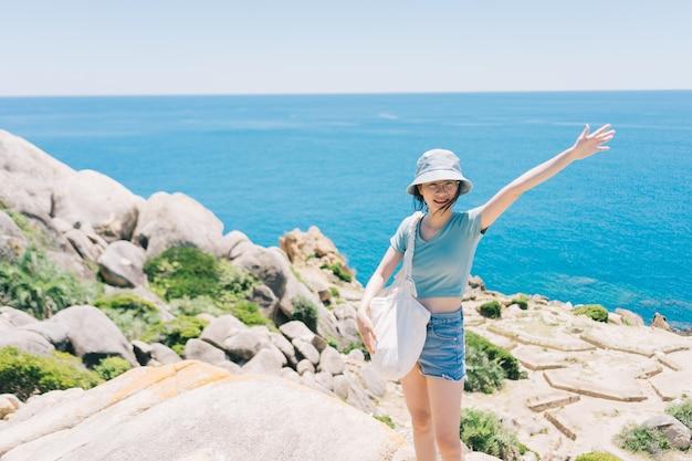 Jovem mulher asiática cumprimentando-se em um penhasco na praia