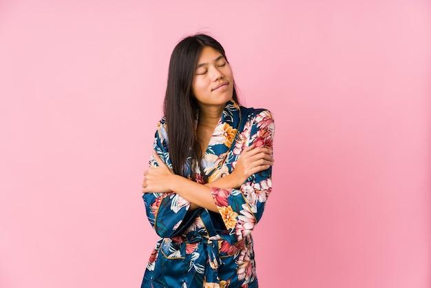 Jovem mulher asiática de pijama de quimono abraços, sorrindo despreocupada e feliz.