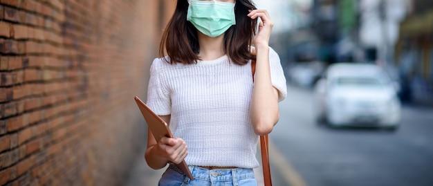 Jovem mulher asiática de trabalho usar máscara cirúrgica com tablet no marco thapae gate da província de chiang mai, tailândia