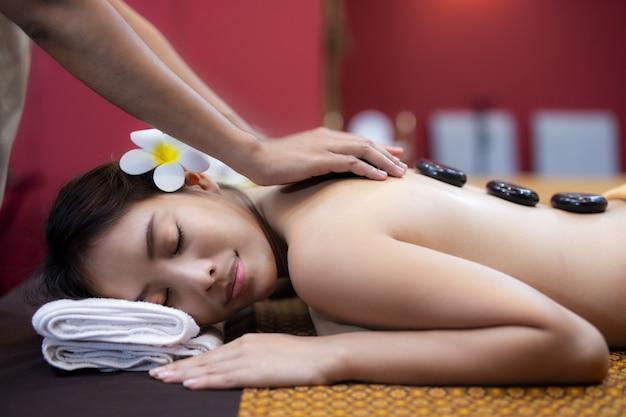 Jovem mulher asiática, deitada na cama em massagem spa.
