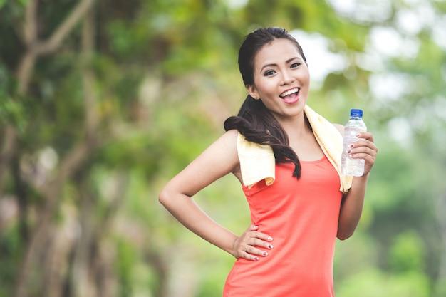 Jovem mulher asiática depois de fazer exercício ao ar livre em um parque