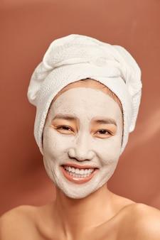 Jovem mulher asiática desfrutando de um tratamento de máscara facial.
