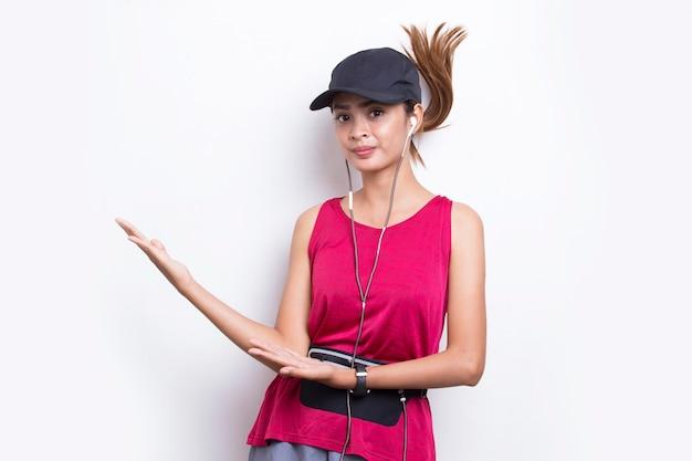 Jovem mulher asiática desportiva apontando o dedo em um espaço vazio no fundo branco