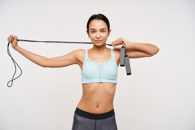 Jovem, mulher asiática desportiva com cabelo comprido escuro. vestindo roupas esportivas e esticando uma corda de pular no pescoço. assistindo confiante para a câmera isolada sobre fundo branco