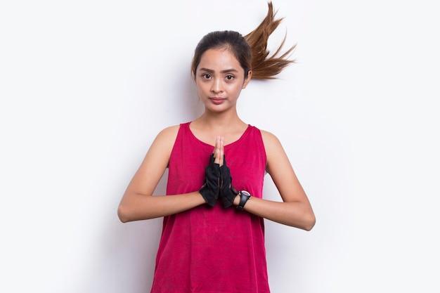 Jovem mulher asiática desportiva mostra gesto de boas-vindas em fundo branco