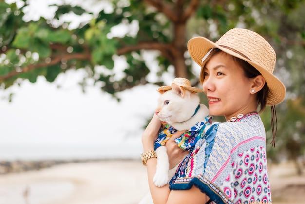 Jovem mulher asiática detém um gato branco sobre o fundo do mar ao ar livre