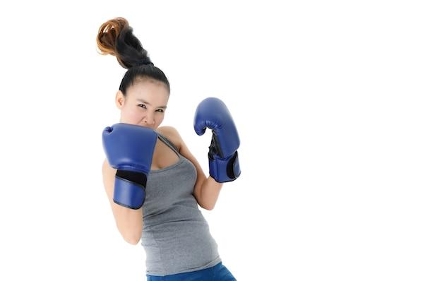 Jovem mulher asiática determinada e forte em luvas de boxe azuis golpeando e perfurando o ar contra um fundo branco
