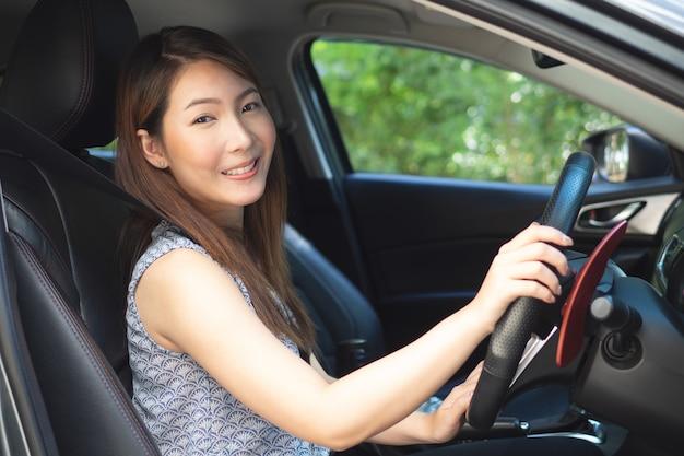 Jovem mulher asiática dirigindo um carro